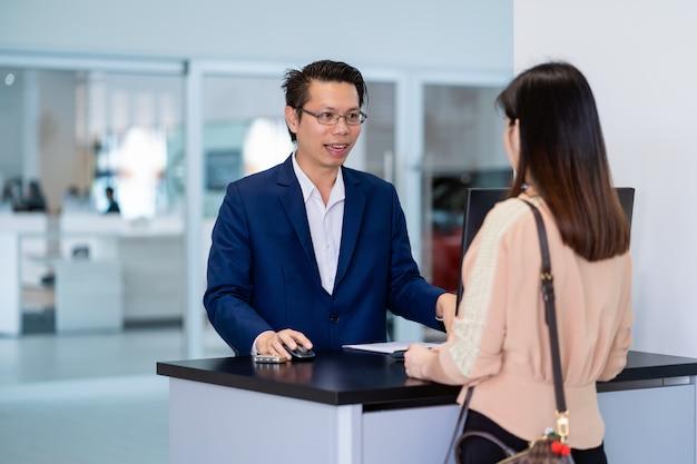 La receptionist asiatica ha ricevuto la chiave automatica dell'auto per il controllo presso il centro servizi di manutenzione per lo showroom Foto Premium
