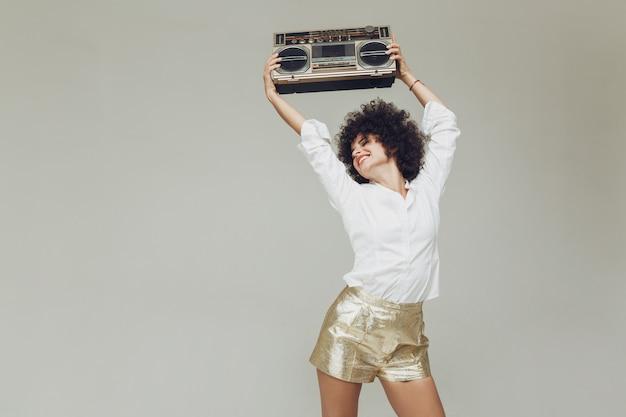 La retro donna impressionabile si è vestita nel boombox della tenuta della camicia. Foto Gratuite