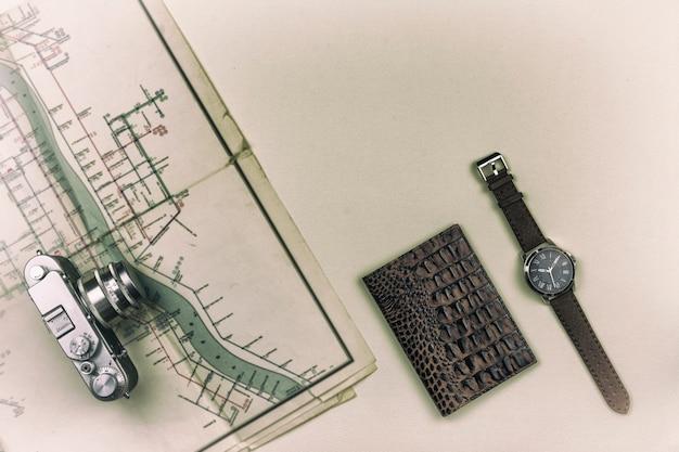 La retro fotocamera è sulla vecchia mappa. il passaporto con un orologio da polso è sul tavolo. viaggio estivo Foto Premium
