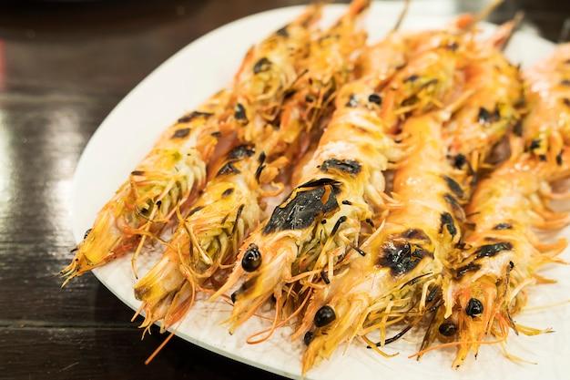 La ricetta del gamberetto arrostito serve in piatto bianco sopra la tavola di legno Foto Gratuite
