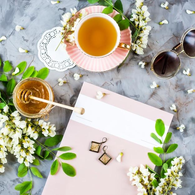 La rivista accanto a una tazza di tè e un barattolo di miele, tra la fioritura di acacia Foto Premium
