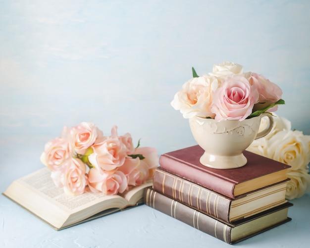 La rosa artificiale di rosa fiorisce in tazza d'annata con i libri sul blu Foto Premium