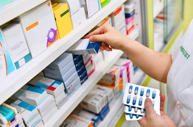 La scatola della medicina della tenuta del farmacista e la capsula imballano nella farmacia della farmacia. Foto Premium