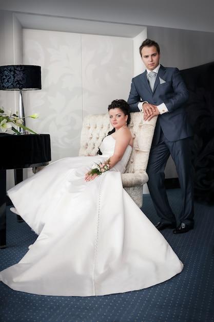 La seduta e lo sposo della sposa stanno su un chai Foto Premium