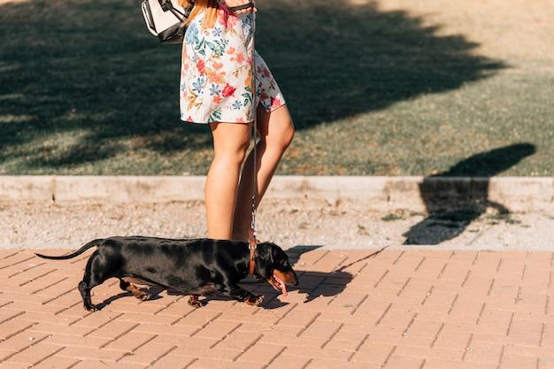 La sezione bassa di una donna con lei cammina sul marciapiede nel parco Foto Gratuite