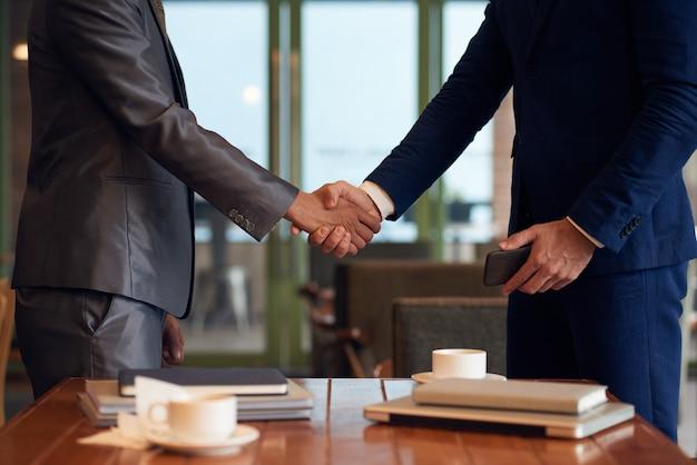 La sezione centrale di due uomini d'affari irriconoscibili si stringono la mano per concludere l'affare Foto Gratuite
