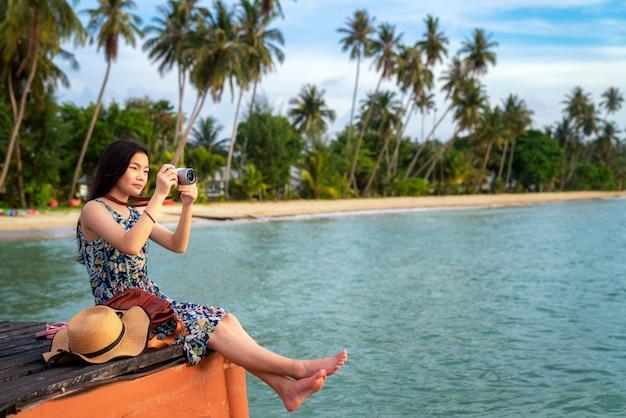 La signora asiatica si rilassa e prende la foto sul ponte boscoso Foto Premium