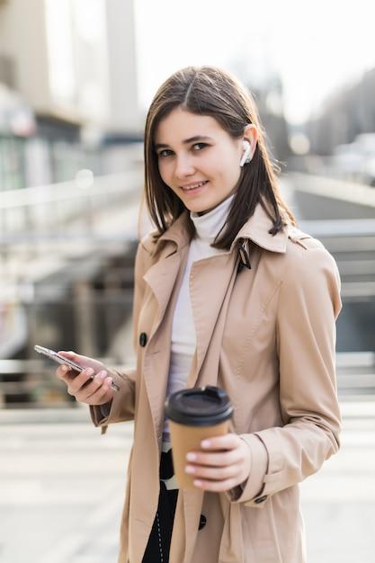 La signora bella beve il caffè e legge le notizie sul suo telefono all'esterno Foto Gratuite