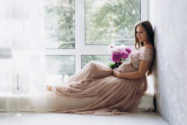 La signora in attesa si trova sul davanzale della finestra in una stanza luminosa Foto Gratuite