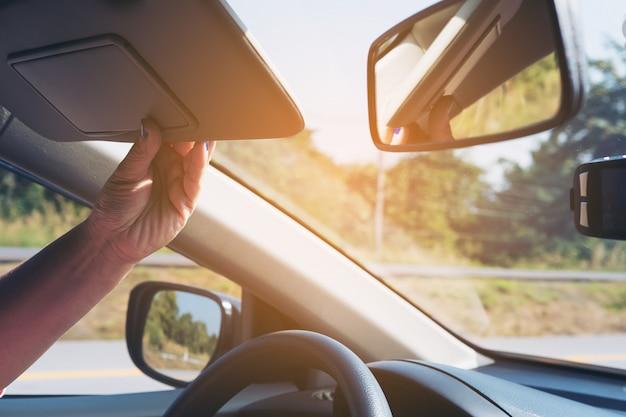 La signora regola l'aletta parasole mentre conduce l'automobile sulla strada della strada principale - automobile interna facendo uso del concetto Foto Gratuite