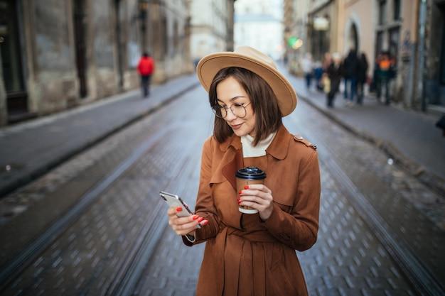 La signora sorridente ha una videochiamata e beve il caffè mentre cammina all'aperto in città Foto Gratuite