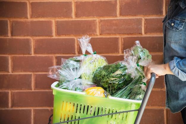 La signora sta acquistando la verdura fresca nel deposito del supermercato Foto Gratuite