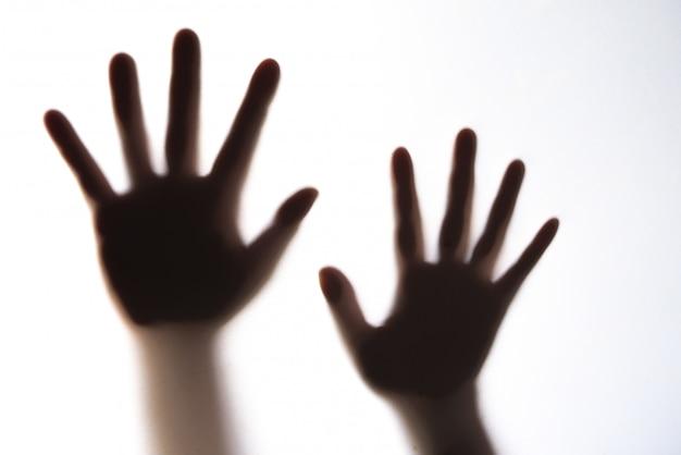 La silhouette della mano di una donna che esprime paura. Foto Premium