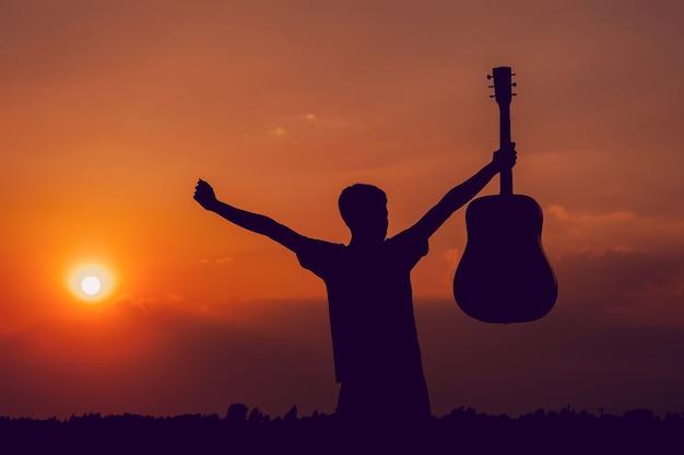 La silhouette di un chitarrista che tiene una chitarra e ha un tramonto Foto Premium