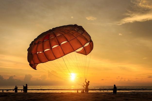 La siluetta dell'uomo sta preparando la navigazione di para alla spiaggia del tramonto in tailandia Foto Premium