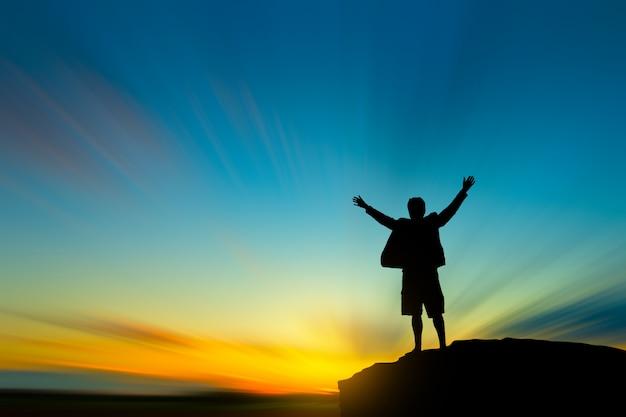 La siluetta dell'uomo sulla cima della montagna sopra cielo e il sole accendono il concetto di successo, della direzione e della gente Foto Premium