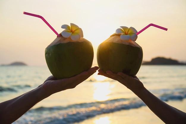 La siluetta della noce di cocco fresca in mani delle coppie con la plumeria ha decorato sulla spiaggia con l'onda del mare - il turista con il concetto di vacanza del sole della sabbia di mare e della frutta fresca Foto Gratuite