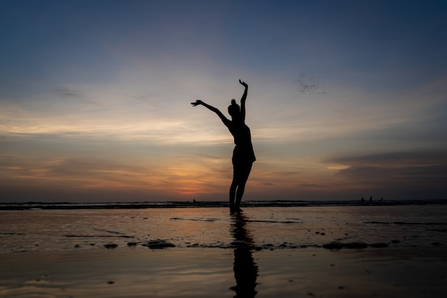 La siluetta di una ragazza che sta nell'acqua con le sue braccia ha sollevato gesturing Foto Gratuite