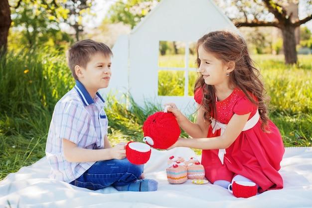 La sorellina del fratello versa il tè in un pic-nic. il concetto di infanzia e stile di vita. Foto Premium