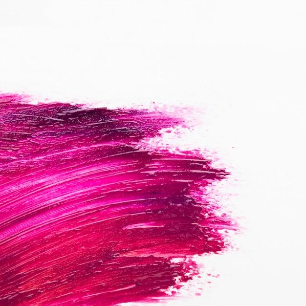 La spazzola rosa brillante dello smalto attacca la superficie bianca Foto Gratuite