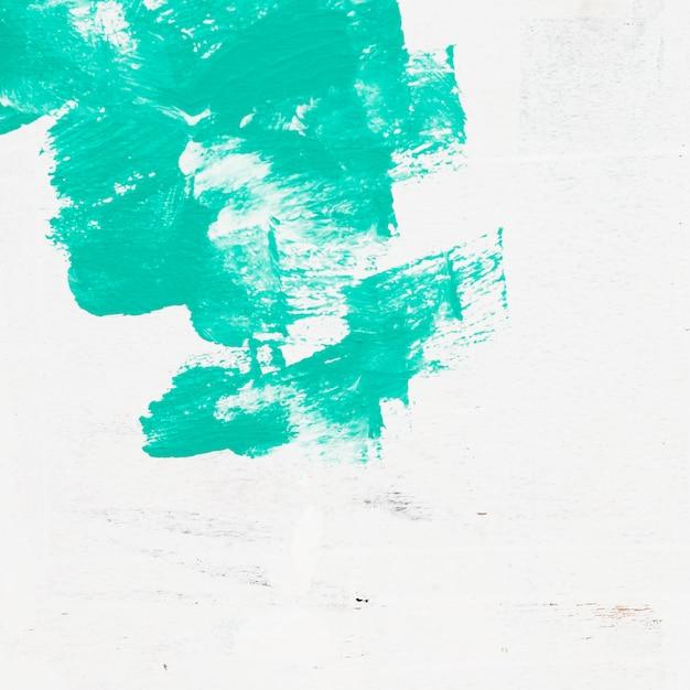 La spazzola verde dell'acquerello segna il fondo su superficie bianca Foto Gratuite