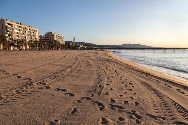 La spiaggia di badalona all'alba con impronte e tracce di auto sulla sabbia Foto Premium