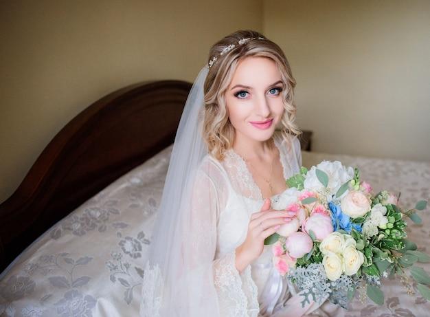 La sposa affascinante in una veste bianca si siede con il mazzo di nozze sulla tavola di cena Foto Gratuite
