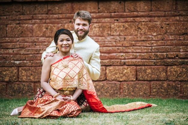 La sposa asiatica e lo sposo caucasico hanno tempo romantico con il vestito della tailandia Foto Gratuite