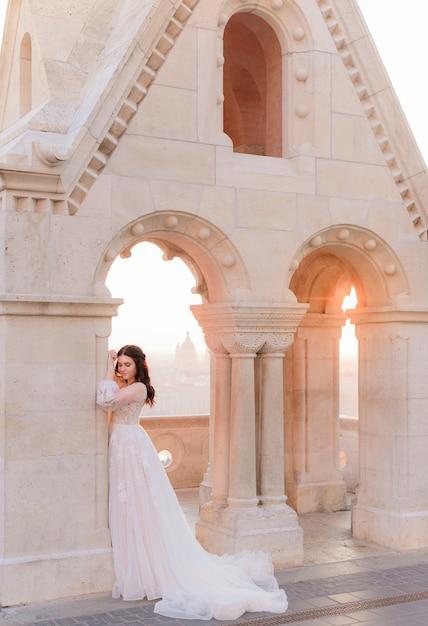 La sposa attraente in tenero vestito alla moda è in piedi vicino alla colonna di pietra in una calda giornata estiva Foto Gratuite