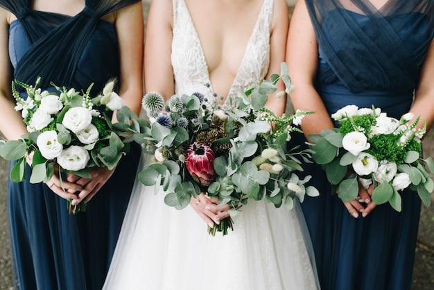 La sposa e le sue damigelle tengono i loro mazzi di fiori di fronte Foto Premium