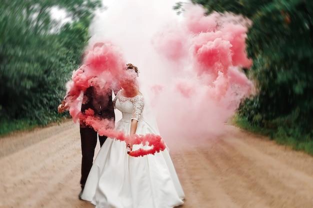 La sposa e lo sposo con il fumo colorato rosso nel parco dell'estate Foto Premium