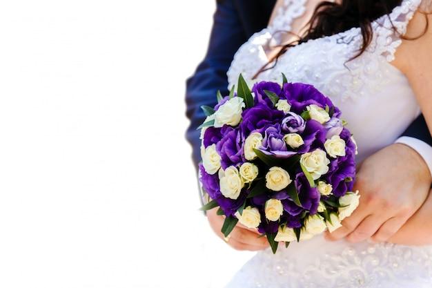 La sposa e lo sposo in possesso di un bouquet da sposa di fiori bianchi e viola Foto Premium