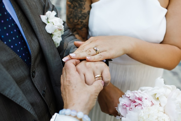 La sposa e lo sposo mostrano le loro mani con le fedi nuziali Foto Gratuite