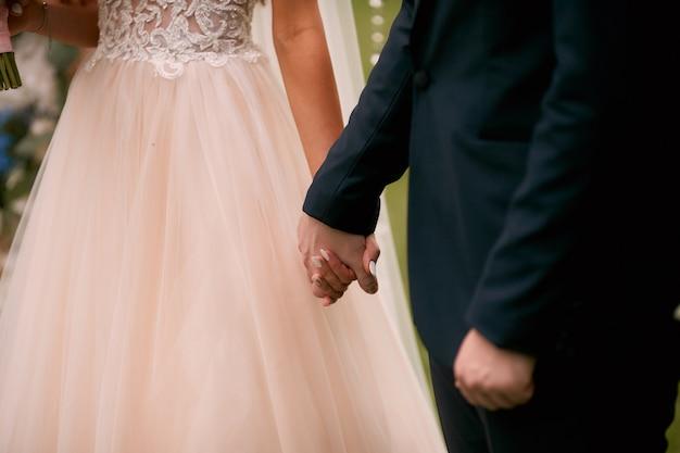 La sposa e lo sposo si tengono per mano in piedi nella chiesa Foto Gratuite
