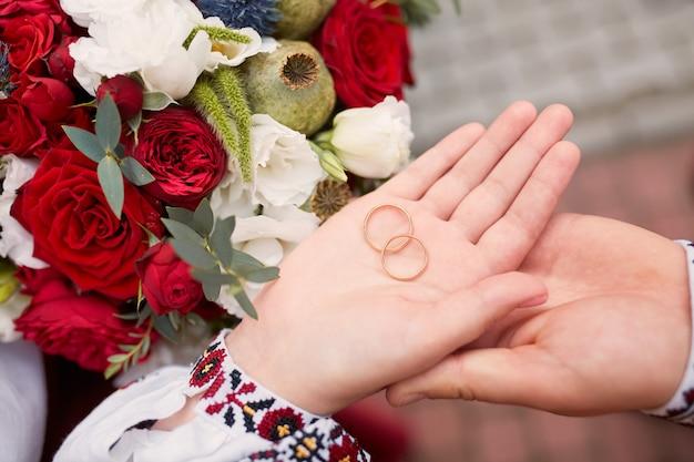 La sposa e lo sposo tengono fedi nuziali tra le loro braccia Foto Gratuite