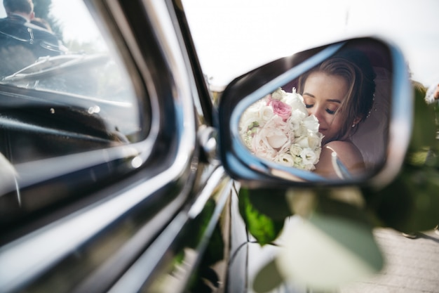 La sposa felice annusa i fiori nell'automobile Foto Gratuite