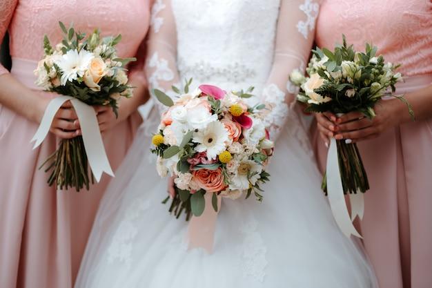 La sposa in abito da sposa bianco detiene bellissimo bouquet da sposa con amiche in abiti rosa Foto Premium