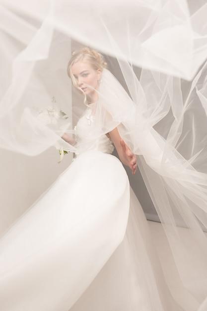 La sposa in bello vestito che sta all'interno nell'interno bianco dello studio gradisce a casa. colpo di stile di nozze alla moda. il giovane modello caucasico attraente gradisce uno sguardo tenero della sposa. Foto Gratuite