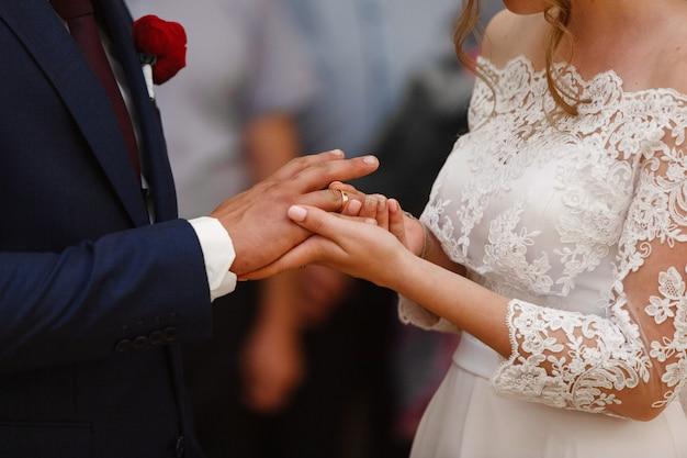 La sposa indossa l'anello nuziale dello sposo. cerimonia di nozze da vicino. sposi si scambiano gli anelli di nozze da vicino. novelli sposi Foto Premium
