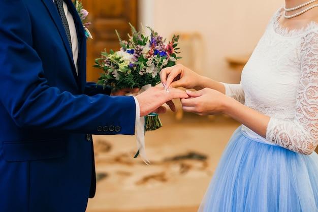La sposa indossa un anello d'oro sul dito dello sposo alle nozze Foto Premium