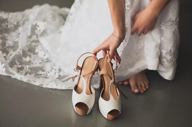 La sposa, la ragazza o la giovane donna in un bellissimo elegante abito da sposa moderno ed elegante cerca scarpe col tacco alla moda leggere da mettere, primo piano. il giorno del matrimonio o la mattina. Foto Premium