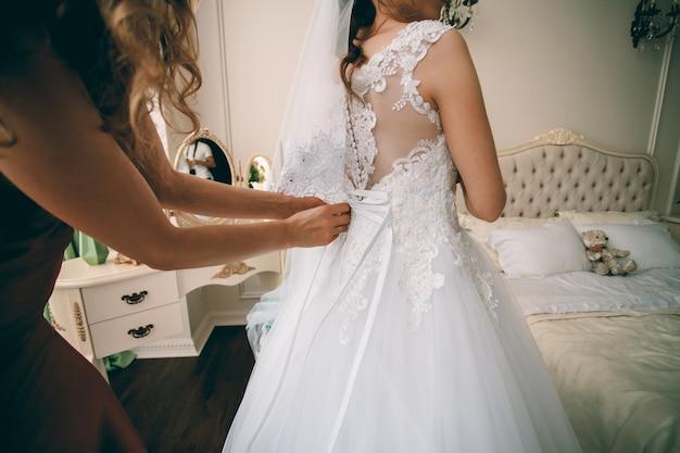 La sposa splendida in vestito di lusso bianco sta preparandosi per le nozze. donna che indossa il vestito Foto Premium