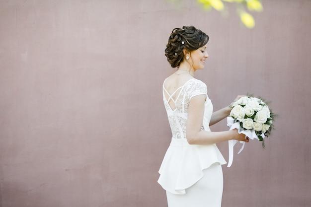 La sposa sta vicino a un muro dell'edificio, tiene un bouquet da sposa e sorride Foto Gratuite