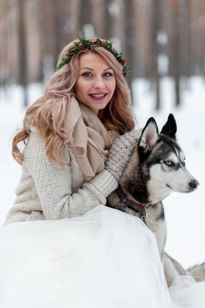 La sposa sveglia con la corona sta giocando con il husky siberiano su fondo di neve bianca. matrimonio invernale. Foto Premium