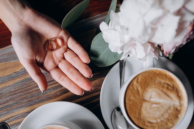 La sposa tiene due anelli di nozze d'oro sul braccio prima di due tazze con il caffè Foto Gratuite