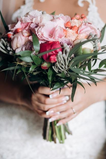 La sposa tiene il bellissimo bouquet da sposa Foto Gratuite