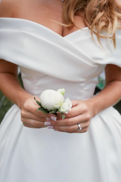 La sposa tiene in braccio un piccolo fiore all'occhiello bianco Foto Gratuite