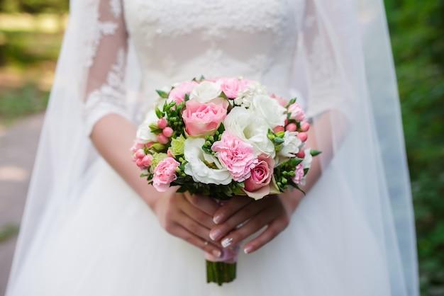 La sposa tiene un bouquet da sposa. Foto Premium