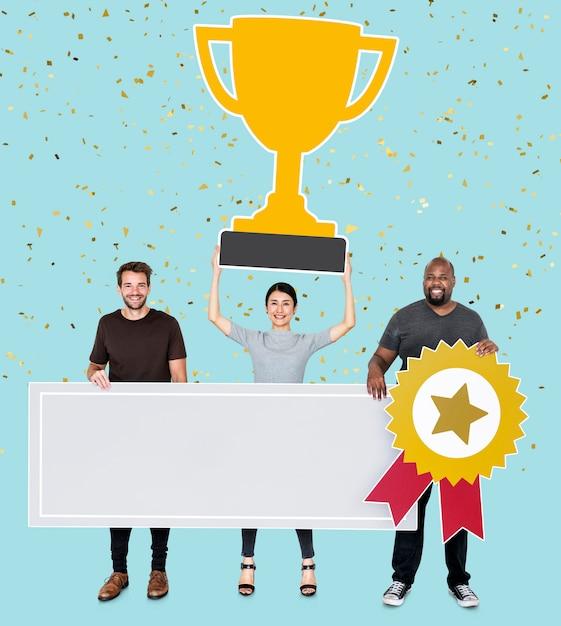 La squadra del vincitore che mostra il loro trofeo e uno spazio della copia Foto Gratuite