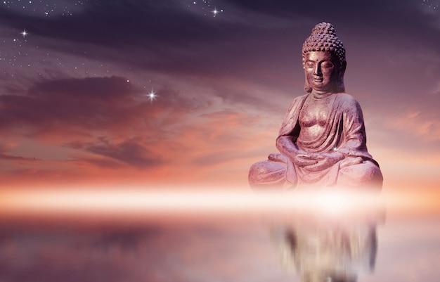 La statua di buddha che si siede nella posa di meditazione contro il cielo del tramonto con i toni dorati si appanna. Foto Premium
